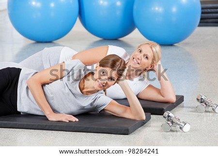 Two happy women relaxing on gym mats in fitness center