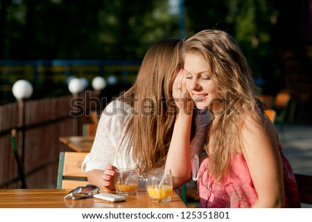 Two happy women sharing secret on cafe terrace by river - stock photo