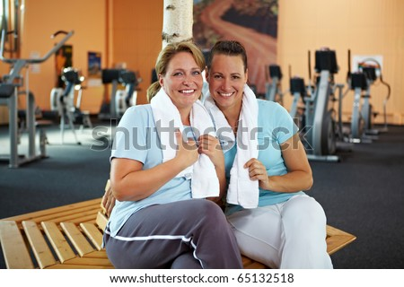 Two happy women talking after their fitness training in gym - stock photo