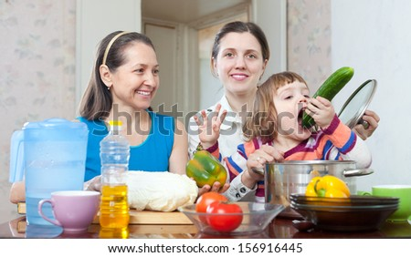 Two happy women with baby girl with vegetables  in kitchen at home - stock photo