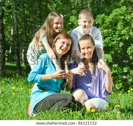 Two happy  women with teens laying on the green grass - stock photo