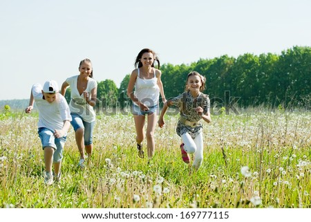 Two happy  women with teens running in grass - stock photo