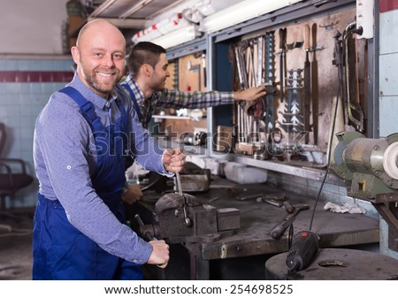 Two happy workmen toiling in locksmiths workshop and smiling  - stock photo