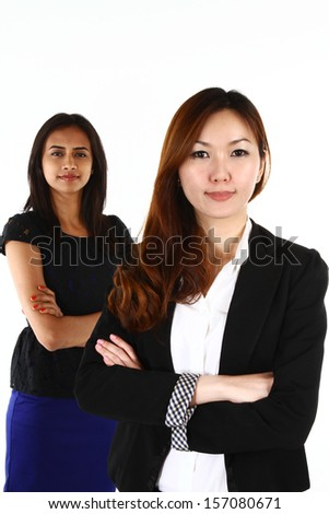 Two happy young Asian business women standing together; on a white background - stock photo