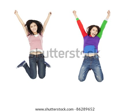 two happy young asian woman jumping with hands up - stock photo