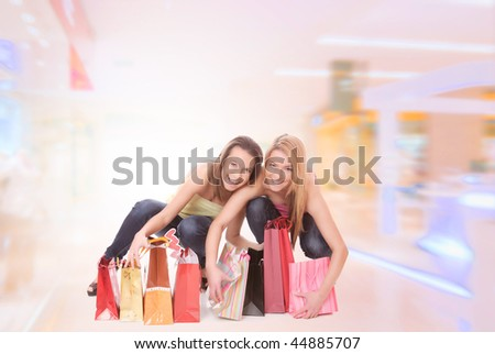 Two happy young beautiful women with the purchases