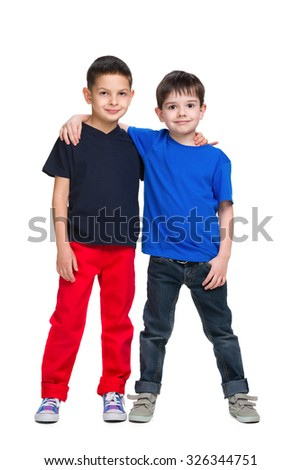 Two happy young boys stand together against the white background - stock photo