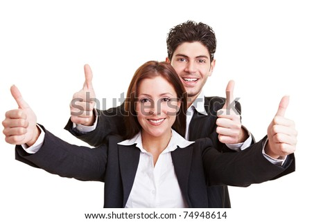 Two happy young business people holding their thumbs up - stock photo