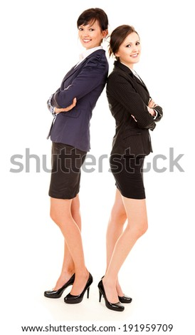 two happy young business women standing and smiling, white background - stock photo