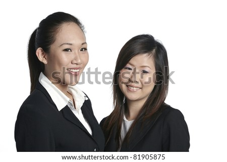 Two happy young business women standing together. Isolated in front of white background - stock photo