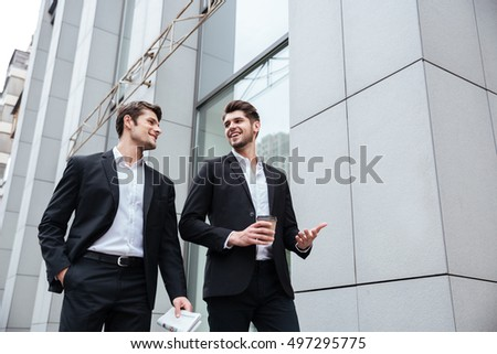Two happy young businessmen walking and talking outdoors
