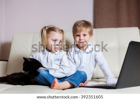 two happy young children: white-skinned boy blond girl sitting with noutbukomego (brother and sister) on a white sofa sit and watch cartoons on your computer - stock photo