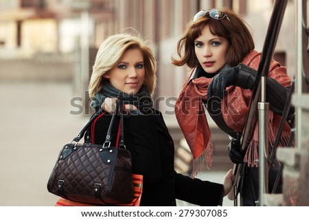 Two happy young fashion women on a city street - stock photo
