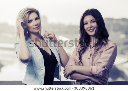 Two happy young fashion women standing on the bridge - stock photo