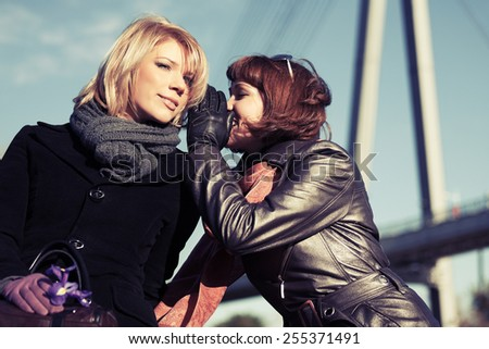 Two happy young fashion women telling secrets outdoor - stock photo