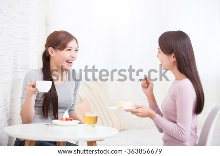 Two happy young female friends with coffee cups and cakes enjoying a conversation in the living room at home, healthy lifestyle concept, asian beauty