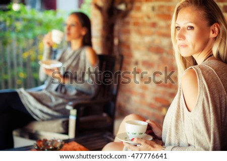 Two happy young female friends with coffee cups enjoying a conversation in a bar