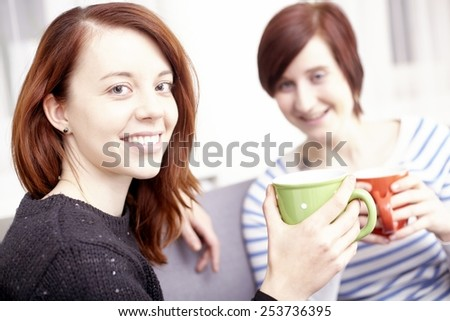 Two happy young female friends with coffee cups enjoying a conversation in the living room at home - stock photo