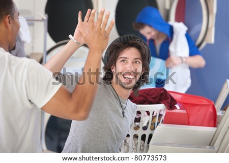 Two happy young friends high five in the laundromat - stock photo