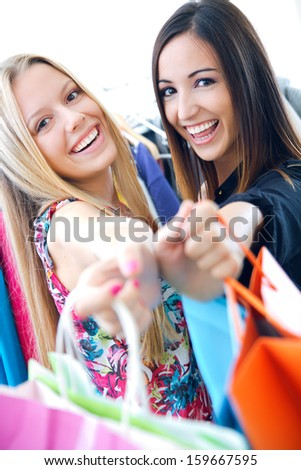 two happy young friends shopping together in town