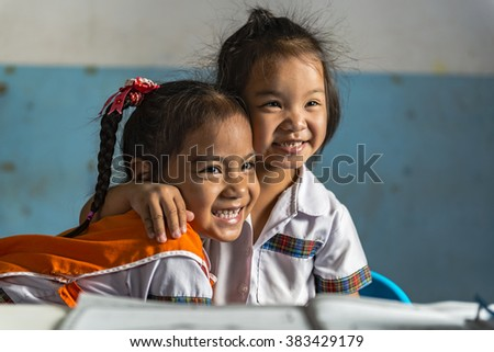 Two happy young girlfriends in the thai school. Thai school in a small village - stock photo