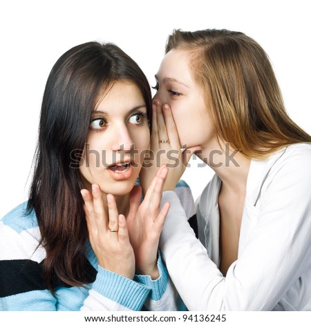 Two happy young girlfriends share secrets - stock photo