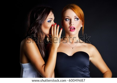 two happy young girlfriends talking over black - stock photo