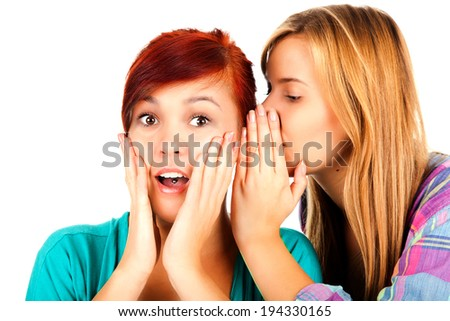 Two happy young girlfriends talking over white.