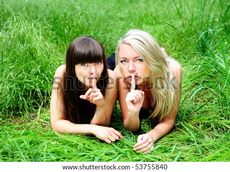 two happy young girlfriends talking secret - stock photo