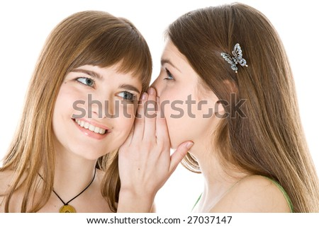Two happy young girlfriends telling secret isolated on white background