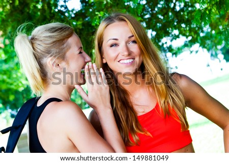 Two happy young girlfriends telling secrets.