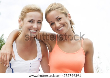 Two happy young girlfriends telling secrets  - stock photo