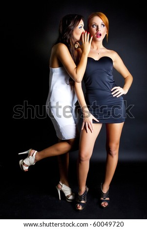 Two happy young girlfriends telling secrets. - stock photo