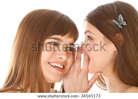 Two happy young girlfriends telling secrets. Isolated on white background - stock photo