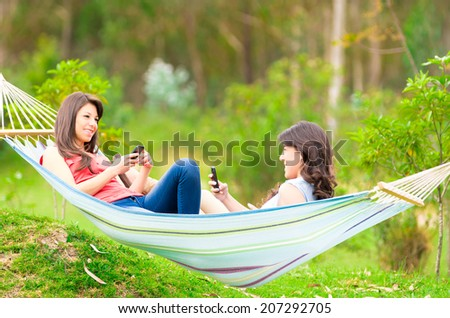 Two happy young girls holding cellphones lying on a hammock - stock photo
