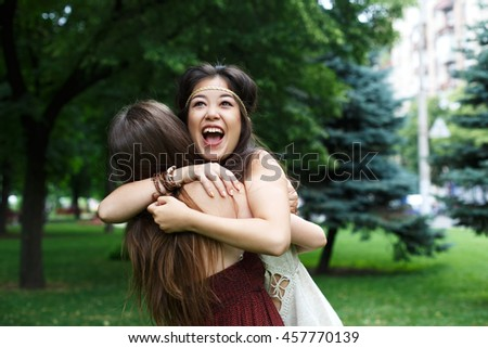 Two happy young girls hug each other. Female friends embracing, laughing and excited. Woman friendship, walk in the park outdoors - stock photo