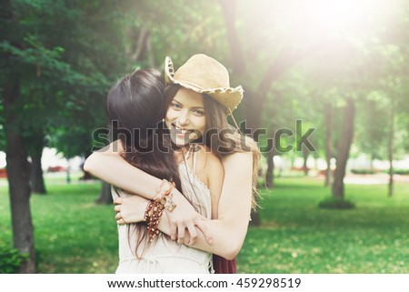 Two happy young girls hug each other. Females embracing, laughing and excited. Woman friendship, walk in the park outdoors. Caucasian boho girl with friend - stock photo