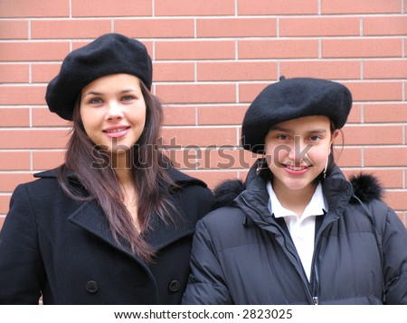 Two happy young girls with beret and coats