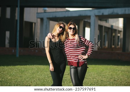 Two happy young smiling woman hugging - stock photo