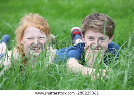 Two happy young teenager lying in a meadow - stock photo