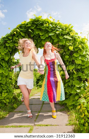 Two happy young women are runing in a park - stock photo