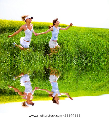 Two happy young women are running in a field
