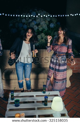 Two happy young women friends dancing and having fun in a outdoors party. Friendship and celebrations concept. - stock photo