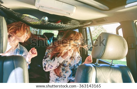 Two happy young women friends dancing and having fun inside of car in a road trip adventure. Female friendship and leisure time concept.  - stock photo