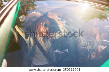 Two happy young women friends with sunglasses dancing and having fun inside of car in a road trip adventure. Female friendship and leisure time concept. - stock photo
