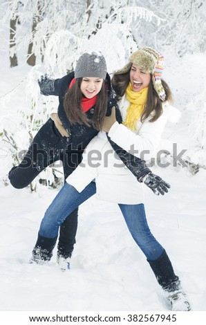 Two happy young women playing in the snow - stock photo