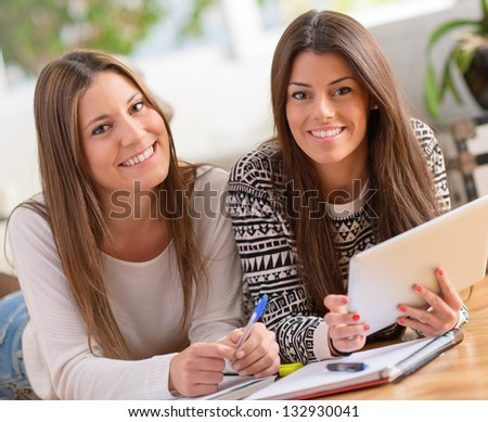Two Happy Young Women With Digital Tablet And Lying On Floor, Indoors - stock photo