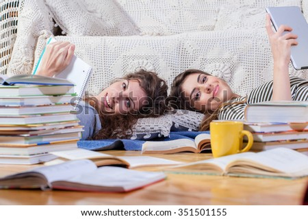 Two happy young women with digital tablet, pen and notebook lying on floor, surrounded with books. - stock photo