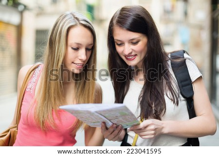 Two happy young women with map chasing city streets and looking for museum