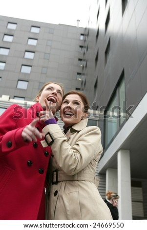 Two happy young women with winter coats, black building background - stock photo